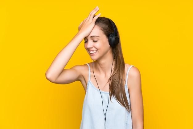 A música de escuta da mulher nova sobre a parede amarela isolada realizou algo e pretendendo a solução