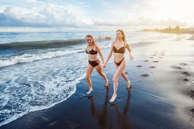 A namorada de duas garotas em maiôs pretos pratica esportes corrida na praia