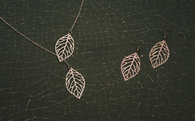 A natureza inspirou o conjunto de acessórios dourados. os colar e brincos da menina emparelham-se em fundo verde rachado.