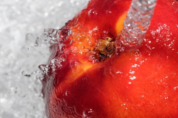 A nectarina madura e doce é lavada sob um jato de macro fotografia de close-up de água limpa