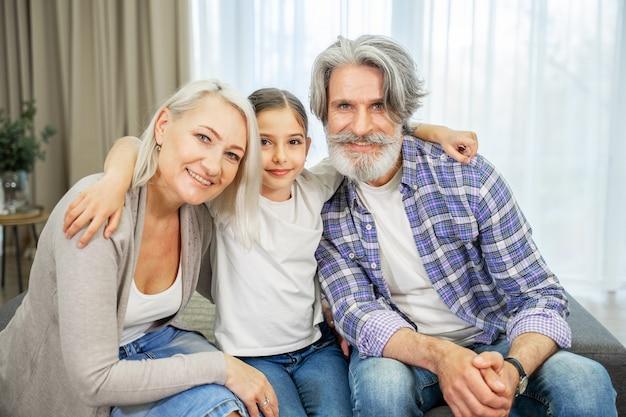 A neta e os avós aposentados sentados no sofá da sala