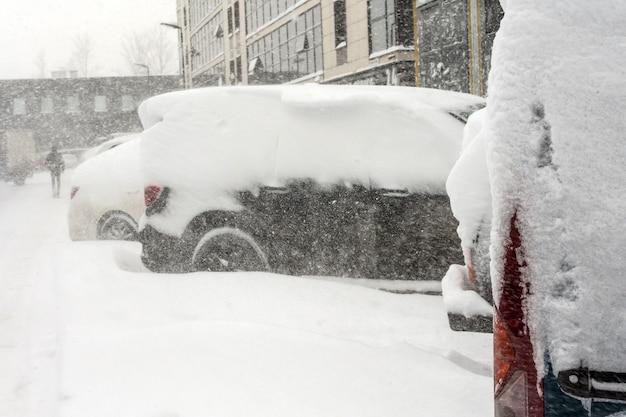 A neve cobriu ows de carros no estacionamento. cena urbana, tempestade de neve. limpe o automóvel da neve.