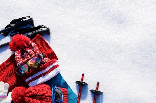 A neve do inverno ostenta o fundo com polos de esqui, óculos de proteção, chapéus e luvas com copyspace.