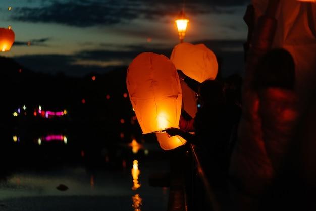 À noite, ao pôr do sol, as pessoas com seus parentes e amigos lançam lanternas tradicionais