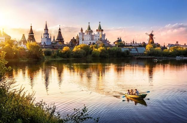 A noite no izmailovsky kremlin em moscou e na lagoa está um barco à vela