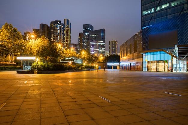 À noite, prédios e praças modernas da cidade ficam no centro financeiro de qingdao, na china.