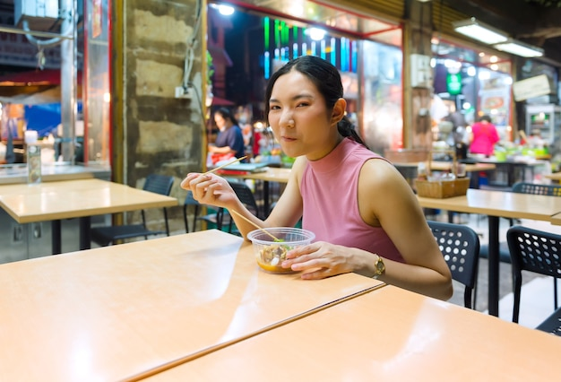 À noite, turistas tailandeses-chineses passeiam e experimentam a comida de rua na yaowarat road, chinatown, bangkok e provam a deliciosa comida de rua. tem frutos do mar, sobremesa, pad thai, macarrão