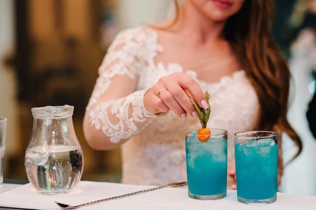 A noiva, a mão da mulher, derrama suco azul fresco no copo fazendo o coquetel