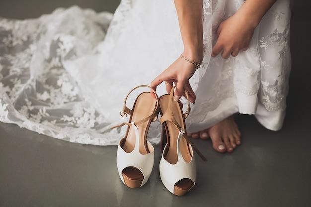 A noiva, a menina ou a jovem mulher em um vestido de casamento à moda moderno elegante bonito alcançam para as sapatas alto-colocadas saltos ligeiras elegantes para pôr sobre, close-up. o dia do casamento ou da manhã.