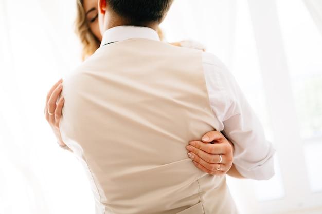 A noiva abraça o noivo com força, o noivo a beija, a vista das costas do noivo