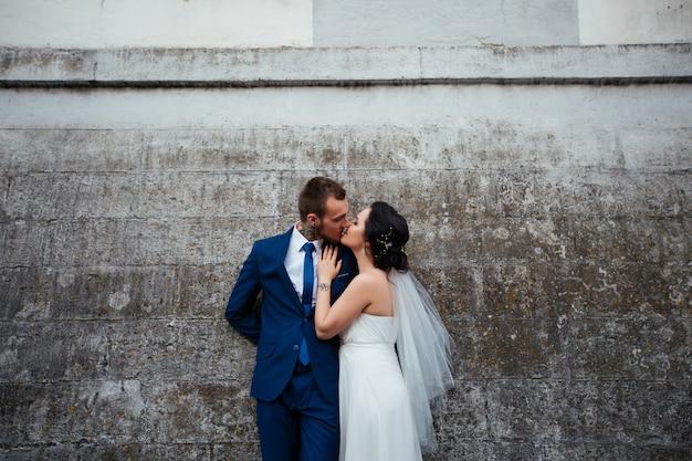 A noiva beijando seu noivo em um fundo de parede cinza