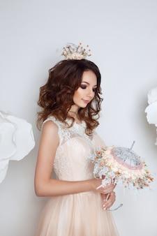 A noiva bonita que levanta no vestido de casamento do pêssego e a flor coroam em um branco. grande decoração de flores brancas