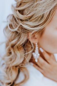 A noiva coloca lindos brincos de casamento. menina com penteado com cachos usando acessórios de joias