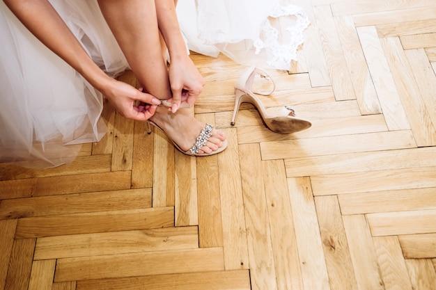 A noiva coloca sapatos de casamento.