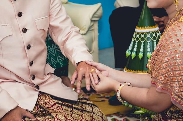 A noiva coloca uma aliança no dedo do noivo, casamento na tailândia.