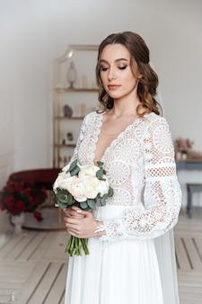 A noiva com um buquê de flores frescas em um lindo vestido festivo com renda. sessão de fotos de casamento, manhã de noiva.