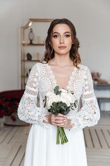 A noiva com um buquê de flores frescas em um lindo vestido festivo com renda.