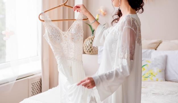 A noiva com um penhoar branco está perto da cama e tem um vestido de noiva nas mãos. foto horizontal