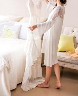 A noiva com um penhoar branco está perto da cama e tem um vestido de noiva nas mãos. foto vertycal