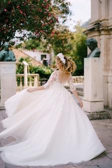 A noiva com uma grinalda girando sob um oleandro em flor perto das esculturas da antiga igreja em