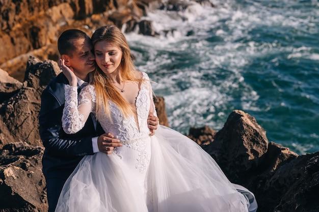 A noiva com vestido de renda branca fechou os olhos e o noivo a abraçou pela cintura