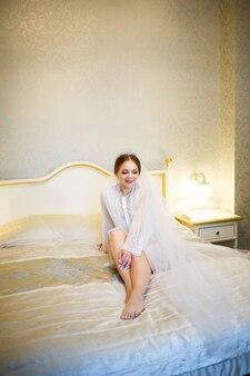 A noiva de jaleco branco na cama em uma manhã de casamento