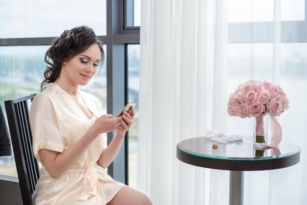 A noiva de manhã sentada à janela com o telefone