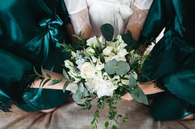 A noiva e as amigas dela seguram um buquê de casamento