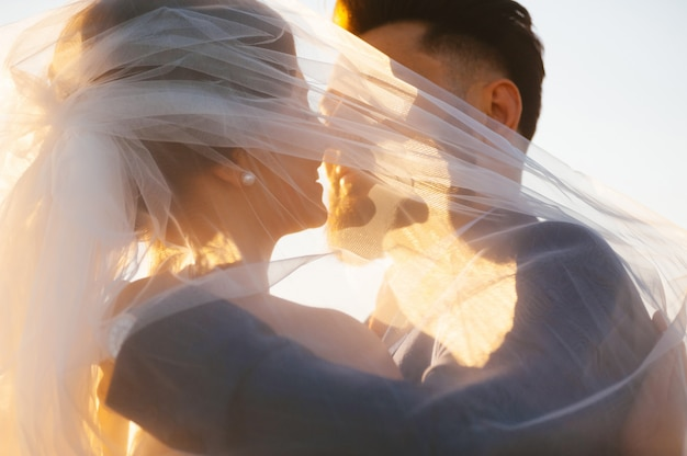 A noiva e o goom quase estão beijando - imagem ascendente próxima na luz do por do sol.