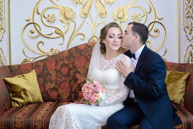 A noiva e o noivo abraçam gentilmente sentado no sofá