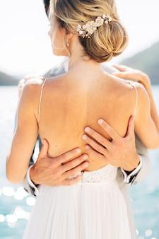 A noiva e o noivo abraçam o noivo colocando as mãos nas costas da noiva.