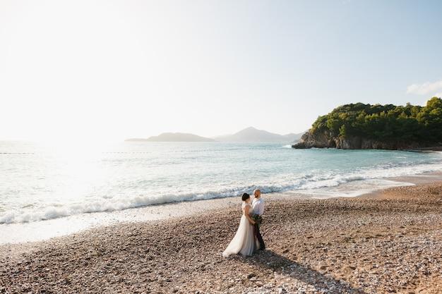 A noiva e o noivo abraçam-se na praia de seixos à beira-mar
