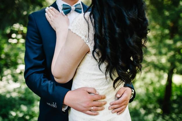 A noiva e o noivo abraçando e de pé na cerimônia de casamento ao ar livre no quintal da natureza.