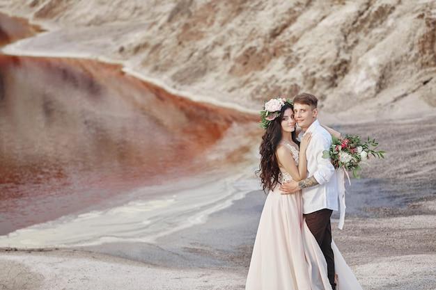 A noiva e o noivo andam ao longo das montanhas vermelhas, cena fabulosa. casal