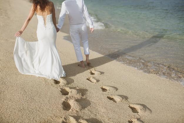 A noiva e o noivo andam de mãos dadas na areia. pegadas na areia perto do oceano