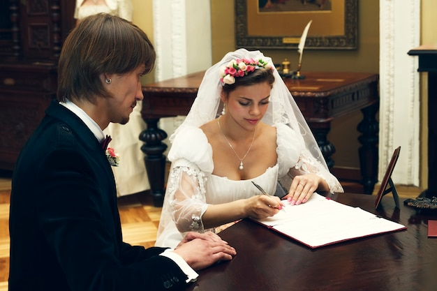 A noiva e o noivo assinam o contrato de casamento