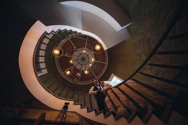 A noiva e o noivo beijando e abraçando em uma escada em espiral. retrato de amar noivos em um belo interior. dia do casamento. conceito de casamento. casado agora mesmo. casal de noivos apaixonado interior