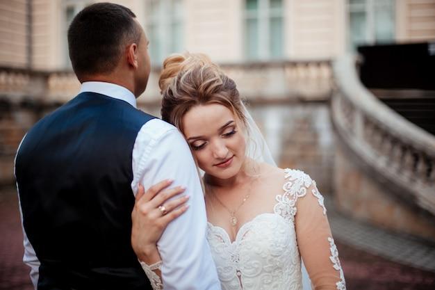 A noiva e o noivo caminham juntos no parque. encantadora noiva em um vestido branco, o noivo está vestido com um terno escuro e elegante.