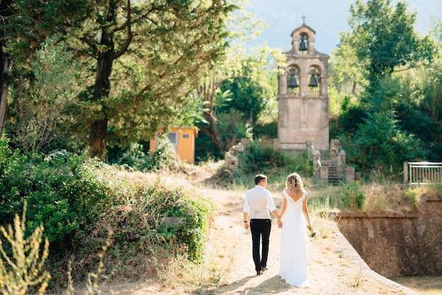 A noiva e o noivo caminham pela estrada iluminada até a antiga torre do sino de mãos dadas