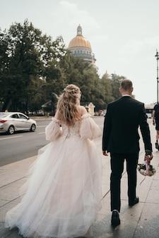 A noiva e o noivo caminham pela rua pelas mãos de um jovem casal estiloso que caminha marido e mulher ...