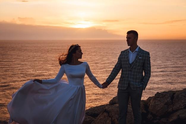 A noiva e o noivo caminhando ao longo da costa rochosa do mar ao pôr do sol
