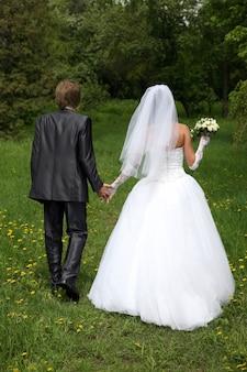 A noiva e o noivo caminhando na grama com flores
