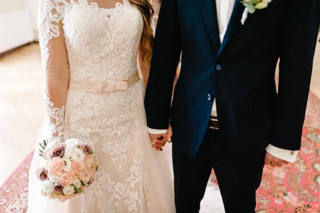 A noiva e o noivo com buquê, segurando as mãos na cerimônia de casamento