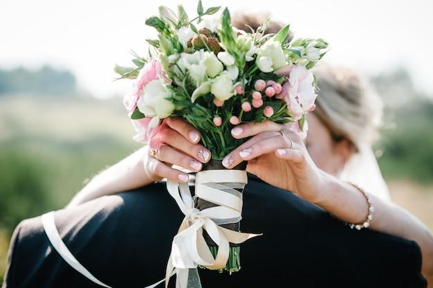 A noiva e o noivo com um buquê de casamento, segurando as mãos e levantando-se na cerimônia de casamento