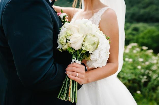 A noiva e o noivo com um buquê de casamento, segurando nas mãos e de pé na cerimônia de casamento ao ar livre no quintal da natureza.