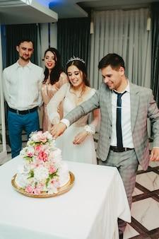 A noiva e o noivo cortam o bolo