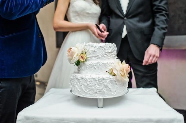 A noiva e o noivo cortam o tradicional bolo de casamento