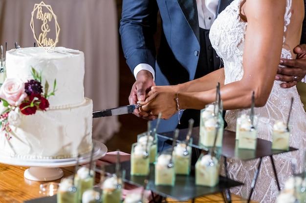 A noiva e o noivo cortando o bolo de casamento