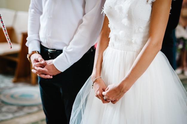 A noiva e o noivo cruzaram as mãos em uma cerimônia de casamento na igreja. vista inferior das mãos.