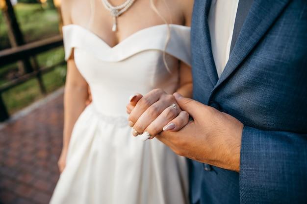 A noiva e o noivo dão as mãos